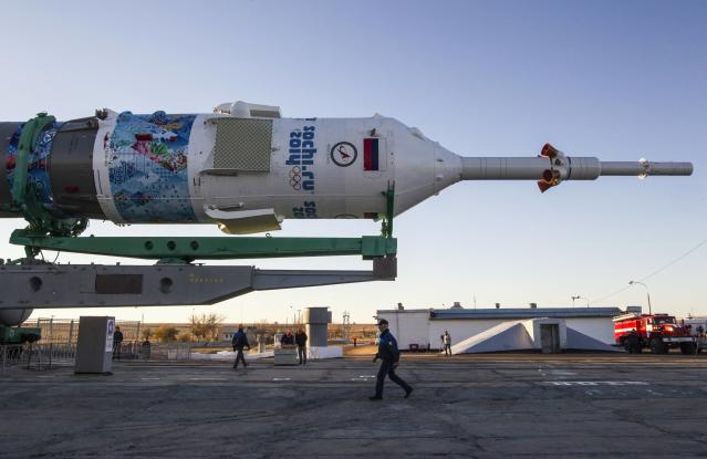 Specialists walk next to the Soyuz TMA-11M spacecraft decorated with 2014 Sochi Winter Olympic Games' patterns, ready to be lifted on its launch pad at the Baikonur cosmodrome November 5, 2013. The Soyuz spacecraft will carry Japanese astronaut Koichi Wakata, Russian cosmonaut Mikhail Tyurin and U.S. astronaut Rick Mastracchio to the International Space Station (ISS) on November 7. REUTERS/Shamil Zhumatov (KAZAKHSTAN - Tags: SCIENCE TECHNOLOGY)