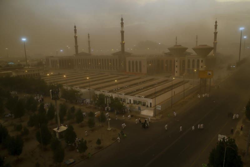 A sand storm engulfs Muslim pilgrims as they arrive at Namirah Mosque on Arafat Mountain, during the annual hajj pilgrimage, outside the holy city of Mecca, Saudi Arabia, Sunday, Aug. 19, 2018. More than 2 million Muslims have begun the annual hajj pilgrimage, representing one of the five pillars of Islam and is required of all able-bodied Muslims once in their life. (AP Photo/Dar Yasin)