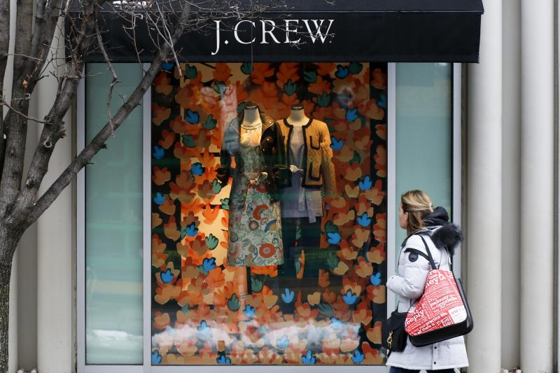 A shopper passes a display in the window of a J. Crew store in the Shadyside shopping district of Pittsburgh.