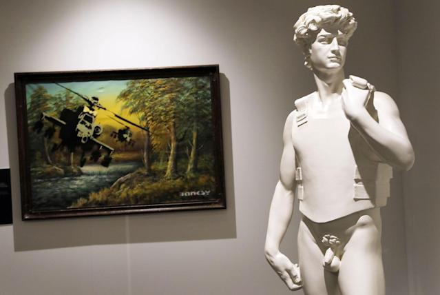 <p>A view of the sculpture 'Bullet Proof David' standing next to the painting entitled 'Happy Chopper Crude Oil' by British Banksy during the exhibition 'The Art of Banksy' in Berlin, Germany on June 20, 2017. (Felipe Trueba/EPA/REX/Shutterstock) </p>