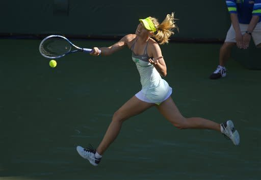 Maria Sharapova, of Russia, returns a shot to Carla Suarez Navarro, of Spain, during their match at the BNP Paribas Open tennis tournament, Sunday, March 10, 2013, in Indian Wells, Calif. (AP Photo/Mark J. Terrill)