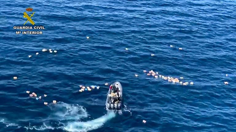 This handout picture released by the Spanish Guardia Civil shows a speedboat surrounded by bundles of drugs in the sea, after a police high-speed chase with drug-smugglers, off the coast of Mijas, Malaga, southern Spain