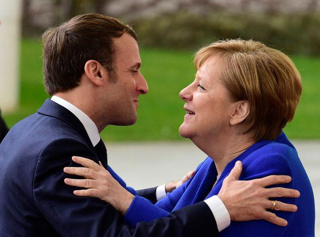German Chancellor Angela Merkel, right, greets French President Emmanuel Macron, center, during arrivals for a conference on Libya at the chancellery in Berlin, Germany, Sunday, Jan. 19, 2020. German Chancellor Angela Merkel hosts the one-day conference of world powers on Sunday in Berlin to discuss efforts to broker peace in Libya. (AP Photo/Jens Meyer)