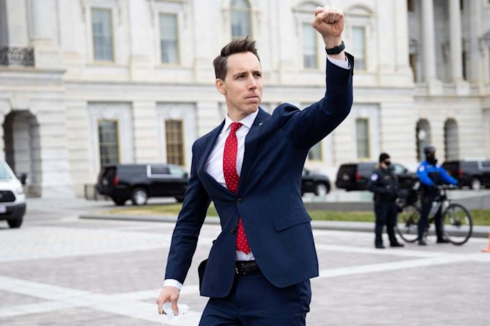 ONE TIME USE 1/7/2021 Sen. Josh Hawley (R-Mo.) gestures toward a crowd of supporters of President Donald Trump gathered outside the U.S. Capitol to protest the certification of President-elect Joe Biden's electoral college victory Jan. 6, 2021 at the US Capitol in Washington, DC. Some demonstrators later breached security and stormed the Capitol.