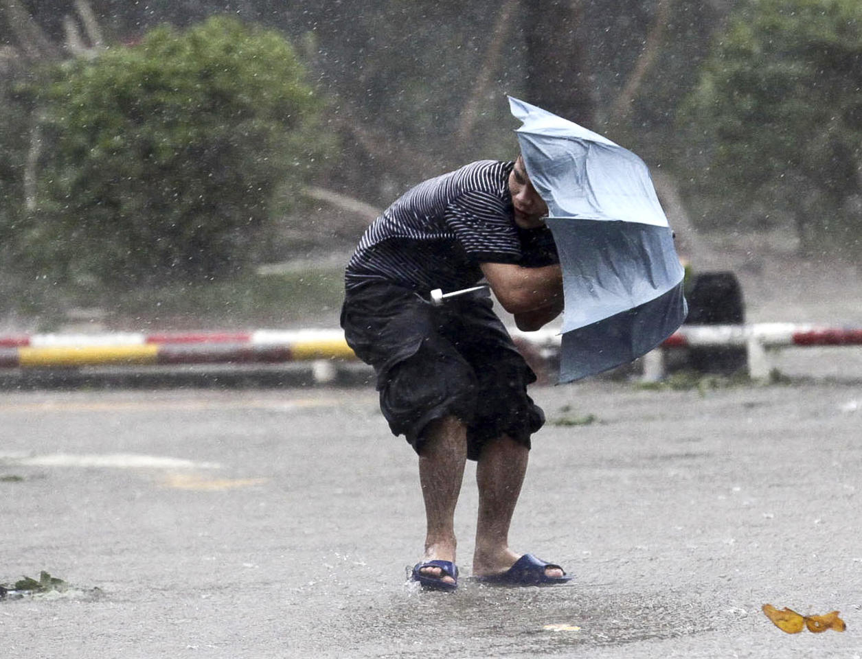A man braves strong winds and rain on a street as typhoon Nesat hits Haikou in south China's Hainan province, Thursday, Sept. 29, 2011. The powerful typhoon slammed into southern China on Thursday after skirting Hong Kong and bringing death and widespread flooding to the Philippines earlier this week. (AP Photo) CHINA OUT