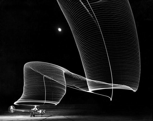"""Feb 01, 1949 - A long exposure view of a Sikorsky S-51 helicopter on the ground at Anacostia Naval Air Station in Washington, DC in 1949. The striking """"Slinky shape"""" is produced by light reflecting on the rotor blades and leaving a trail in the night sky. Photo: Andreas Feininger/Time & Life Pictures/Getty Images."""
