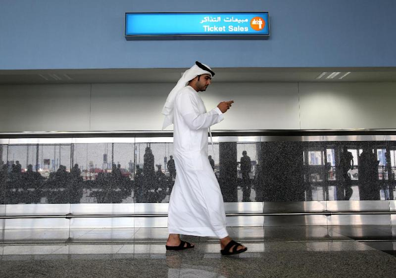 A worker looks at his mobile phone at the newly opened Al Maktoum International Airport in Dubai, United Arab Emirates, Sunday, Oct. 27, 2013. The first passengers have arrived at Dubai's newest airport, part of the United Arab Emirates' plans to become a major air travel destination. The new airport is known by the code DWC for Dubai World Center. (AP Photo/Patrick Castillo, Emarat Al Youm)