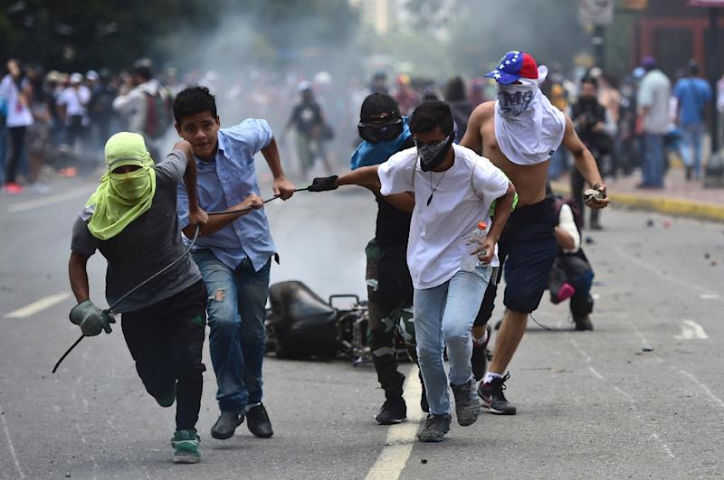 Anti-government activists drag a police motorbike burnt after the explosion of an explosive device during a protest against the elections for a Constituent Assembly in Caracas on July 30, 2017 (AFP Photo/Ronaldo SCHEMIDT)