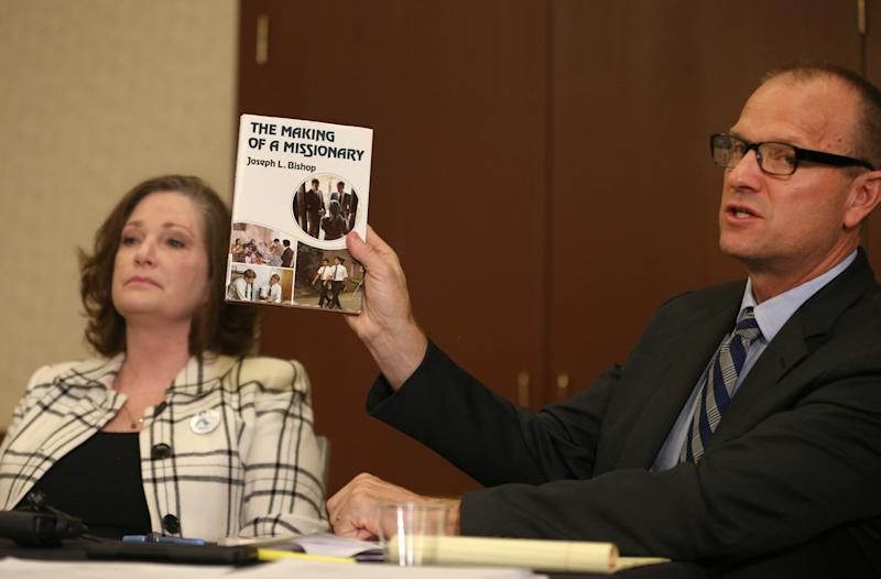 Attorney Craig Vernon holds up a book by Joseph L. Bishop at a news conference on April 5, 2018, in Salt Lake City. (George Frey/Getty Images)