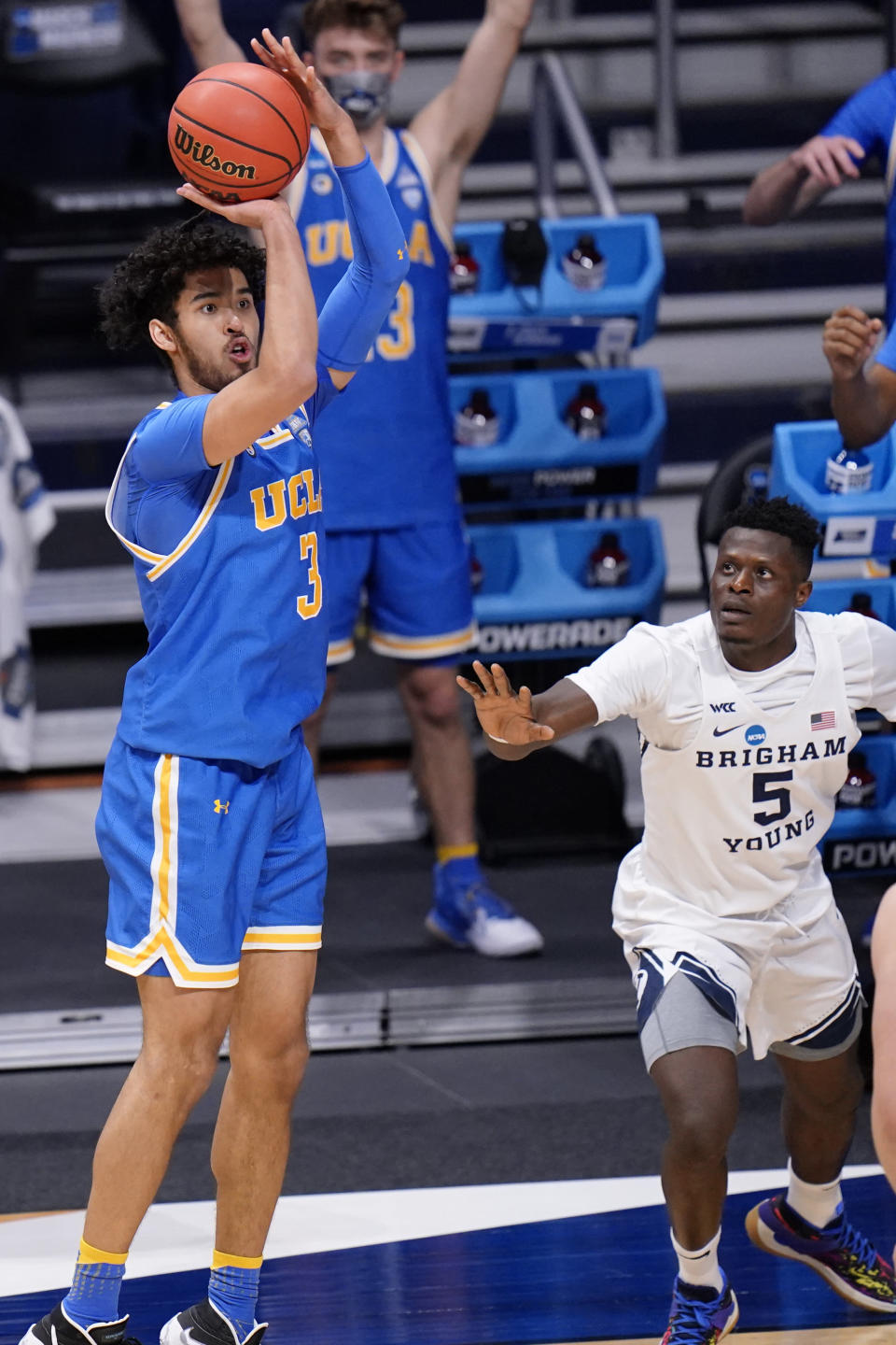 UCLA guard Johnny Juzang (3) takes a three point shot as BYU forward Gideon George (5) defends during the second half of a first-round game in the NCAA college basketball tournament at Hinkle Fieldhouse in Indianapolis, Saturday, March 20, 2021. (AP Photo/AJ Mast)