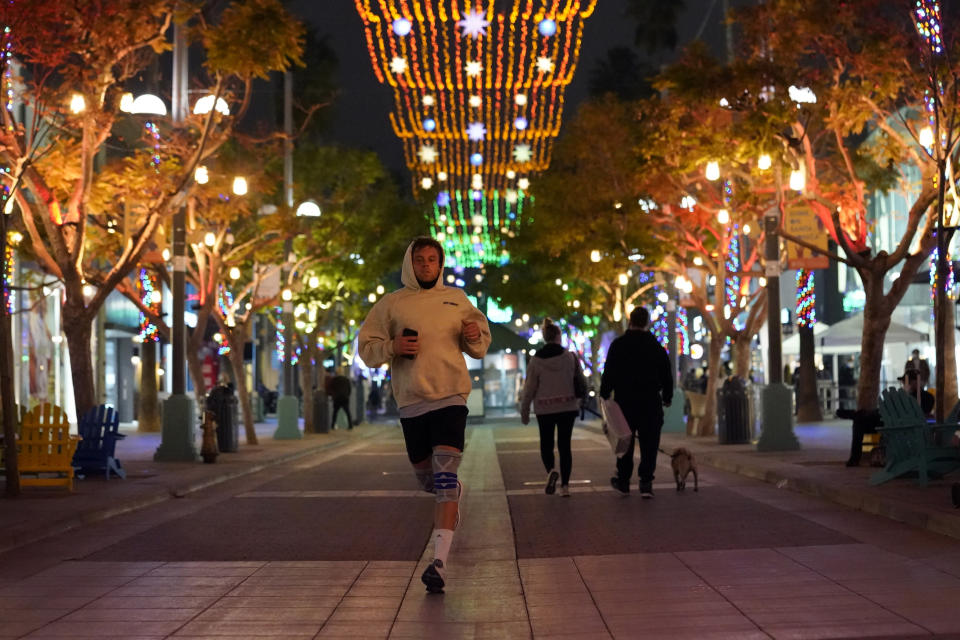 FILE - In this Nov. 19, 2020, a jogger runs through a shopping district in Santa Monica, Calif. California Gov. Gavin Newsom is imposing an overnight curfew as the most populous state tries to head off a surge in coronavirus cases. On Thursday, Newsom announced a limited stay-at-home order in 41 counties that account for nearly the entire state population of just under 40 million people. (AP Photo/Marcio Jose Sanchez, File)