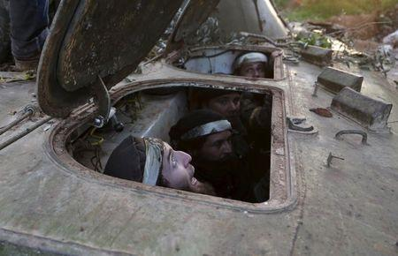 Rebel fighters from the Ahrar al-Sham Islamic Movement sit inside a BMP armoured vehicle during what they said was an offensive to take the northwestern city of Idlib March 24, 2015. REUTERS/Khalil Ashawi
