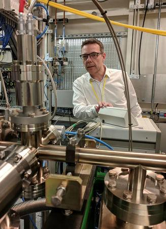 Professor John McGeehan, an X-ray Crystallographer at the University of Portsmouth, stands next to equipment at the Diamond Light Source, the UK national synchrotron, that he used to reveal the atomic structure of an enzyme his team has subsequently engineered that can digest a common form of plastic and may in future help in the fight against pollution, in Didcot, Britain, April 13, 2018. REUTERS/Stuart McDill