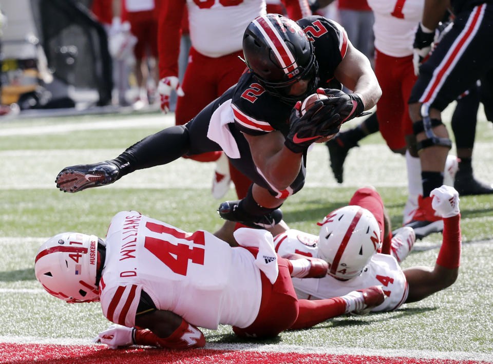 Ohio State running back J.K. Dobbins, top, dives into the end zone over Nebraska defenders Deontai Williams, left, and Tre Neal during the first half of an NCAA college football game Saturday, Nov. 3, 2018, in Columbus, Ohio. (AP Photo/Jay LaPrete)