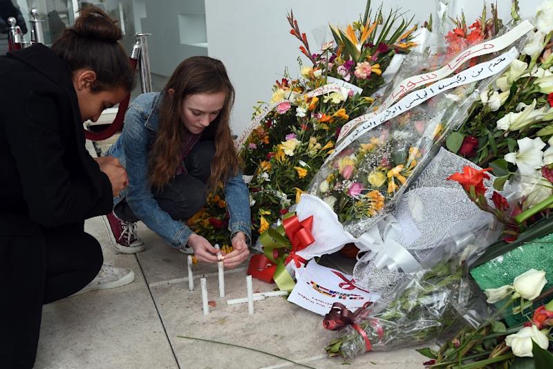 Tourists light candles at the national Bardo Museum in Tunis in memory of the victims of the March attack