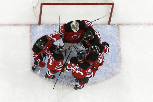 New Jersey Devils players huddle with goaltender Keith Kinkaid, top, while celebrating a 3-2 victory over the Carolina Hurricanes during an NHL hockey game, Sunday, Feb. 10, 2019, in Newark, N.J. (AP Photo/Julio Cortez)