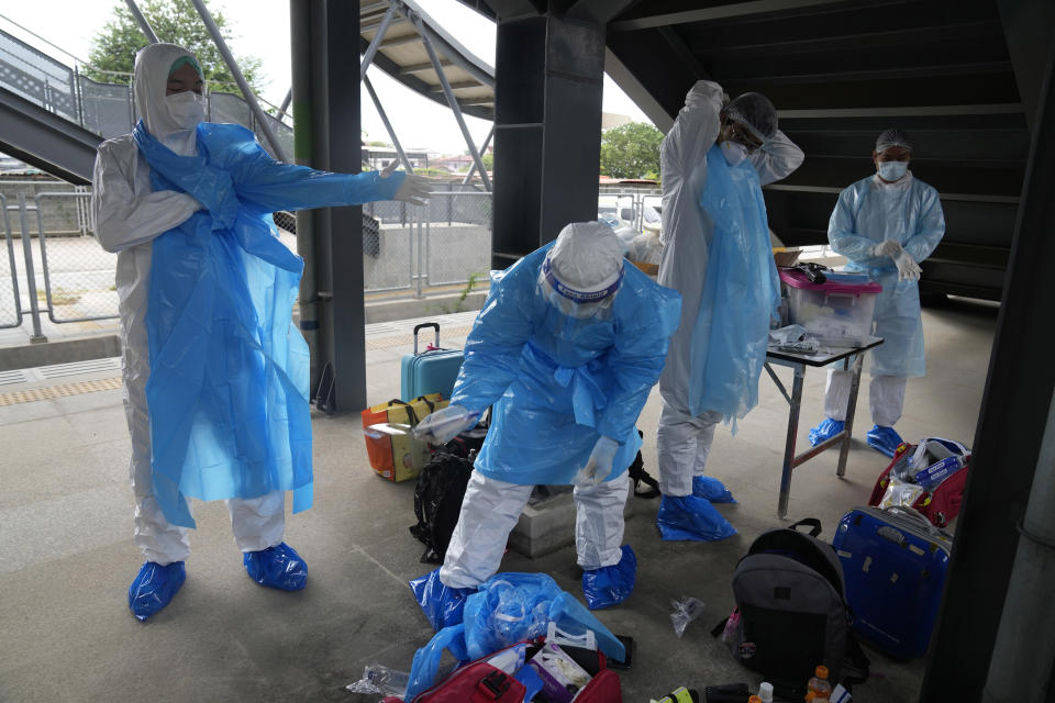 Health workers prepare their protective gear before a group of people infected with COVID-19 arrive at Rangsit train station in Pathum Thani Province, Thailand, Tuesday, July 27, 2021. Thai authorities began transporting some people who have tested positive with the coronavirus from Bangkok to their hometowns on Tuesday for isolation and treatment, to alleviate the burden on the capital's overwhelmed medical system. (AP Photo/Sakchai Lalit)