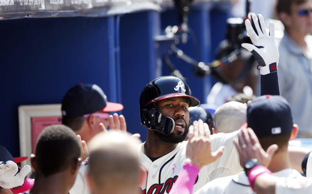 Atlanta Braves' Jason Heyward, center, celebrates with teammates in the dugout after hitting a two-run home run in the seventh inning of a baseball game against the Chicago Cubs, Sunday, May 11, 2014, in Atlanta. (AP Photo/John Bazemore)