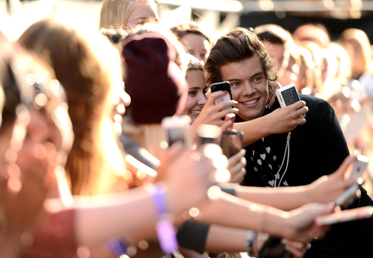 "LONDON, ENGLAND - AUGUST 20: Singer Harry Styles from One Direction poses with fans as he attends the ""One Direction This Is Us"" world premiere at the Empire Leicester Square on August 20, 2013 in London, England. (Photo by Ian Gavan/Getty Images for Sony Pictures)"