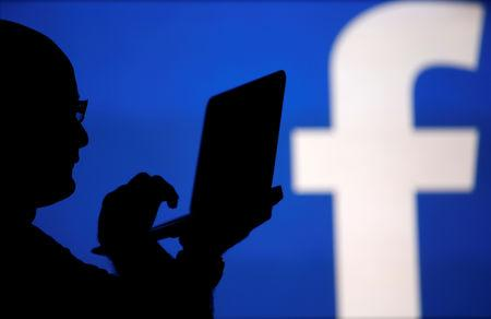 A man is silhouetted against a video screen with an Facebook logo in this photo illustration in Zenica