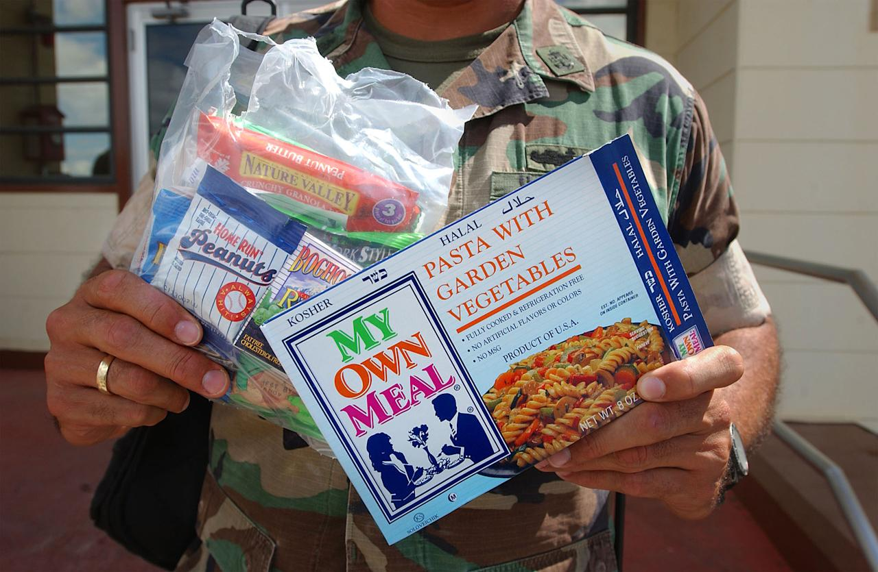 400671 11: A U.S. Marine displays the daily lunch ration for Taliban and Al Qaeda detainees at Camp X-Ray February 6, 2002 in Guantanamo Bay, Cuba. There are 156 Al Qaeda and Taliban prisoners currently being held in the camp, and they are given three Muslim-friendly meals a day. (Photo by Chris Hondros/Getty Images)