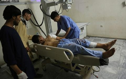 A wounded man receives treatment at a hospital after an explosion at wedding hall in Kabul - Credit: AP
