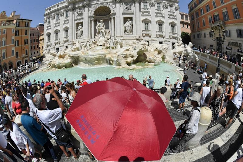 Sightseers shelter from the sun under an umbrella in front of Trevi fountain in Rome as temperatures reached more than 40 degrees Celsius