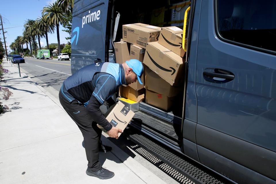 Joseph Alvarado picks up a package while making deliveries for Amazon during the outbreak of the coronavirus disease (COVID-19) in Costa Mesa, California, U.S., March 23, 2020.      REUTERS/Alex Gallardo