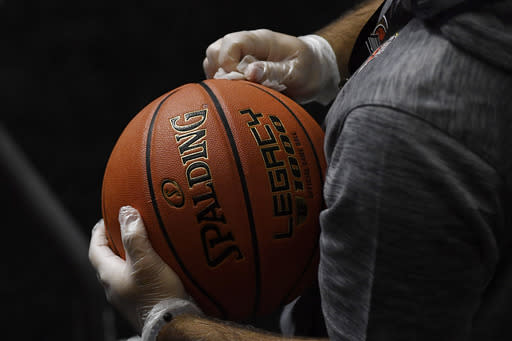 Basketballs, to be used in an upcoming NCAA college basketball game between San Francisco and Virginia, are disinfected with alcohol wipes, Friday, Nov. 27, 2020, in Uncasville, Conn. (AP Photo/Jessica Hill)