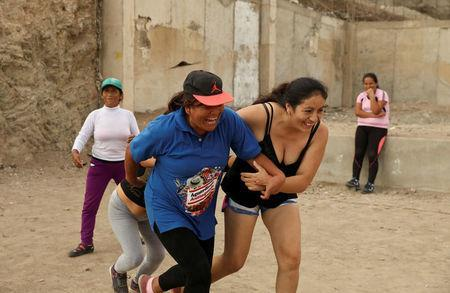 Martha Injusta (L) and Leydi Condor, residents of Nueva Union shantytown, play a volleyball match at a makeshift soccer field in Villa Maria del Triunfo district of Lima, Peru, April 25, 2018. REUTERS/Mariana Bazo