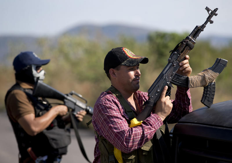 Armed men belonging to the Self-Defense Council of Michoacan, (CAM), stands guard at checkpoint at the entrance of Antunez, Mexico, Tuesday, Jan. 14, 2014. The Mexican government moved in to quell violence between vigilantes and a drug cartel, and witnesses say several unarmed civilians were killed in an early Tuesday confrontation. (AP Photo/Eduardo Verdugo)