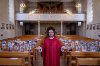 FILE - In this April 4, 2020 file photo, Priest Christian Rauch stands in front of photos with parishioners in the catholic St. Andreas church in Lampertheim, Germany. Due to the coronavirus no services are held these days. More than 50,000 people have died after contracting COVID-19 in Germany, a number that has risen swiftly over recent weeks as the country has struggled to bring down infection figures. (AP Photo/Michael Probst, File)