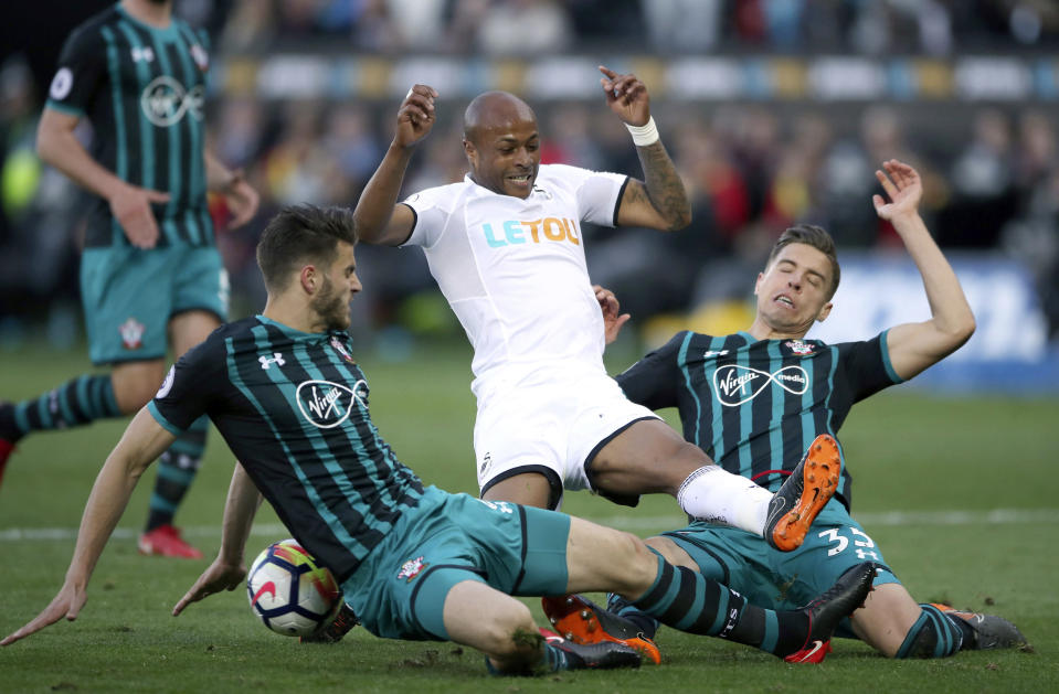 Swansea City's Andre Ayew battles for the ball with Southampton's Jan Bednarek, right, and Wesley Hoedt during the English Premier League soccer match at the Liberty Stadium, Swansea, Wales, Tuesday May 8, 2018. (Nick Potts/PA via AP)