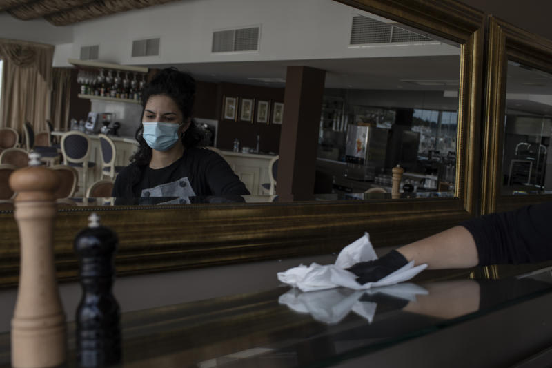 Hotel worker Nikoleta Vafiadou wearing a mask to reduce the spread of the coronavirus cleans at the Acropolian Spirit Hotel in central Athens on Monday June 1, 2020. Lockdown restrictions were lifted on non-seasonal hotels Monday as the country prepares to start its tourism season on June 15. (AP Photo/Petros Giannakouris)