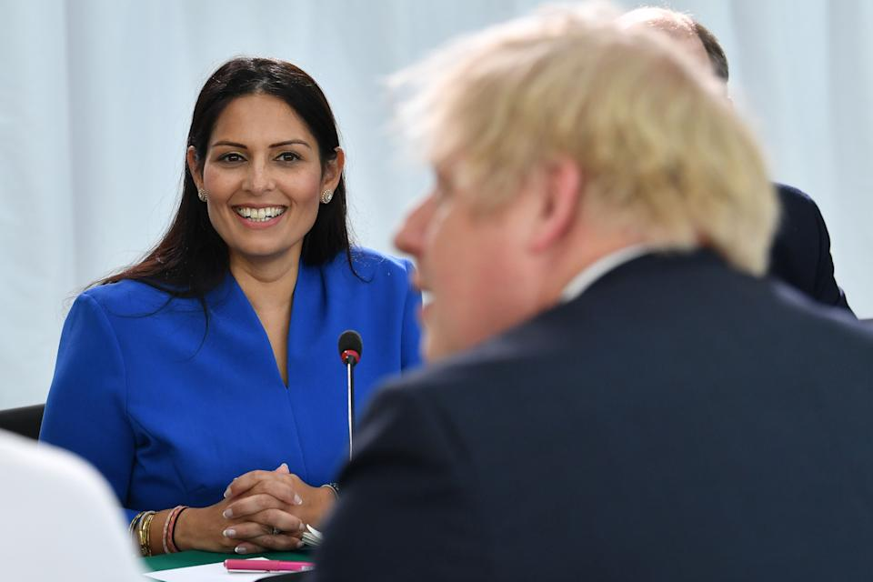 Britain's Home Secretary Priti Patel (L) looks on as Britain's Prime Minister Boris Johnson chairs a cabinet meeting at the National Glass Centre at the University of Sunderland, in Sunderland, northeast England on January 31, 2020, the day that the UK formally leaves the European Union. - Britain on January 31 ends almost half a century of integration with its closest neighbours and leaves the European Union, starting a new -- but still uncertain -- chapter in its long history. (Photo by Paul ELLIS / POOL / AFP) (Photo by PAUL ELLIS/POOL/AFP via Getty Images)