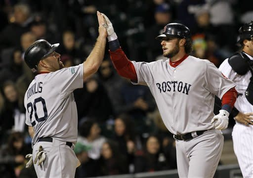 Boston Red Sox's Kevin Youkilis (20) greets teammate Jarrod Saltalamacchia at home after the pair scored on Saltalamacchia's second home run of the game, both off Chicago White Sox starting pitcher Philip Humber, during the fifth inning of a baseball game on Thursday, April 26, 2012, in Chicago. (AP Photo/Charles Rex Arbogast)