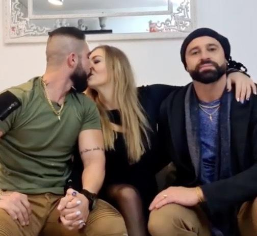 Throuple kiss sitting on couch