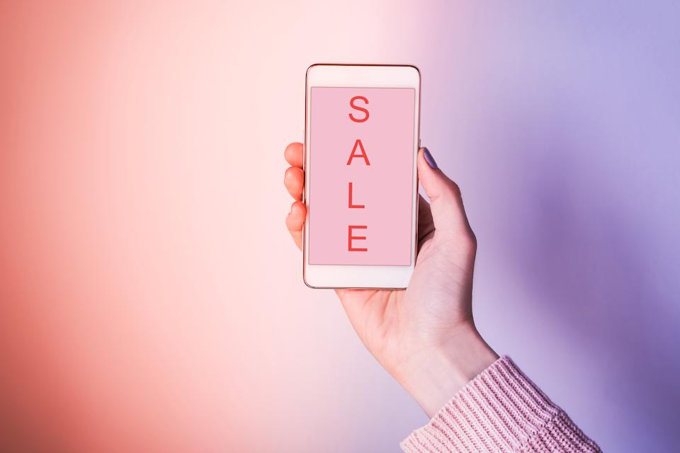 Close-Up Of Woman Hand Holding Mobile Phone Showing Sale Text Against Colored Background