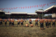 Wrestlers watch as others compete on the third and last day of the 660th instalment of the annual Historic Kirkpinar Oil Wrestling championship, in Edirne, northwestern Turkey, Sunday, July 11, 2021.Thousands of Turkish wrestling fans flocked to the country's Greek border province to watch the championship of the sport that dates to the 14th century, after last year's contest was cancelled due to the coronavirus pandemic. The festival, one of the world's oldest wrestling events, was listed as an intangible cultural heritage event by UNESCO in 2010. (AP Photo/Emrah Gurel)