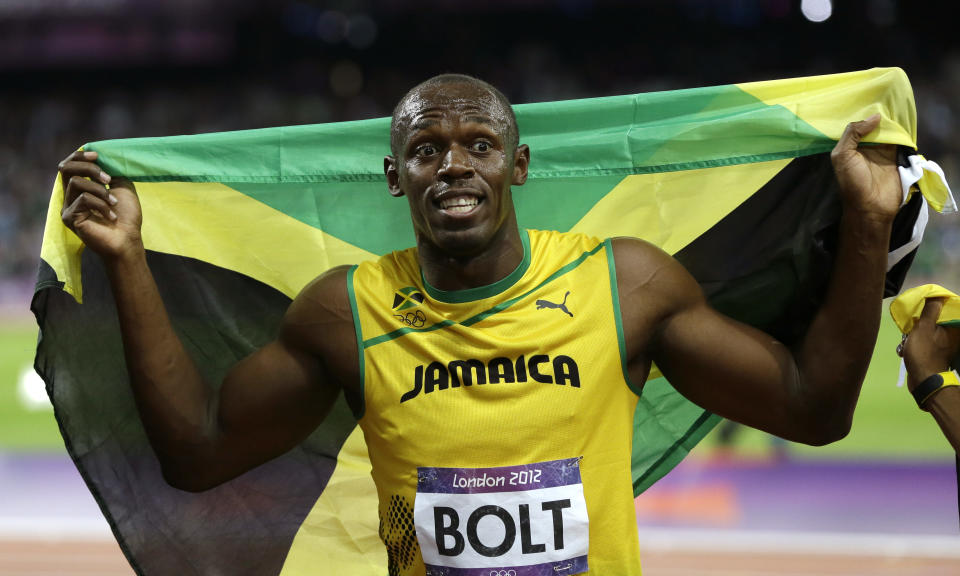 Jamaica's Usain Bolt holds his national flag following his win in the men's 100-meter final during the athletics in the Olympic Stadium at the 2012 Summer Olympics, London, Sunday, Aug. 5, 2012. (AP Photo/Kirsty Wigglesworth)