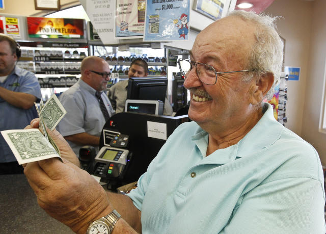 Wes Prinzen, of Fountain Hills, Ariz., smiles as he takes away his modest $4 winnings, at a 4 Sons Food Store where one of the winning tickets in the $579.9 million Powerball jackpot was purchased, Nov. 29, 2012, in Fountain Hills, Ariz. (AP Photo/Ross D. Franklin)