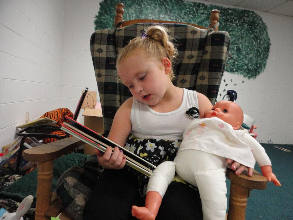 Alana (Honey Boo Boo) reads a book to her baby doll.