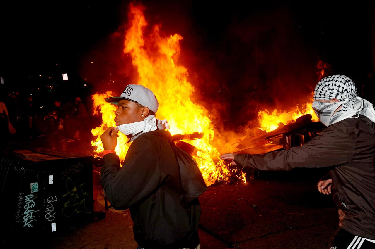 Occupy Oakland protesters pass a burning garbage heap during a confrontation with police on Thursday, Nov. 3, 2011, in Oakland, Calif. Following a mainly peaceful day-long protest by thousands of anti-Wall Street demonstrators, several hundred rallied through the night with some painting graffiti, breaking windows and setting file to garbage cans. (AP Photo/Noah Berger)