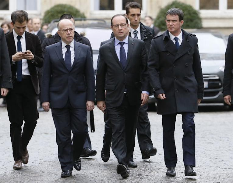 French President Francois Hollande (C) leaves the Interior Ministry in Paris with Prime Minister Manuel Valls (R) and Interior Minister Bernard Cazeneuve (L) after crisis talks