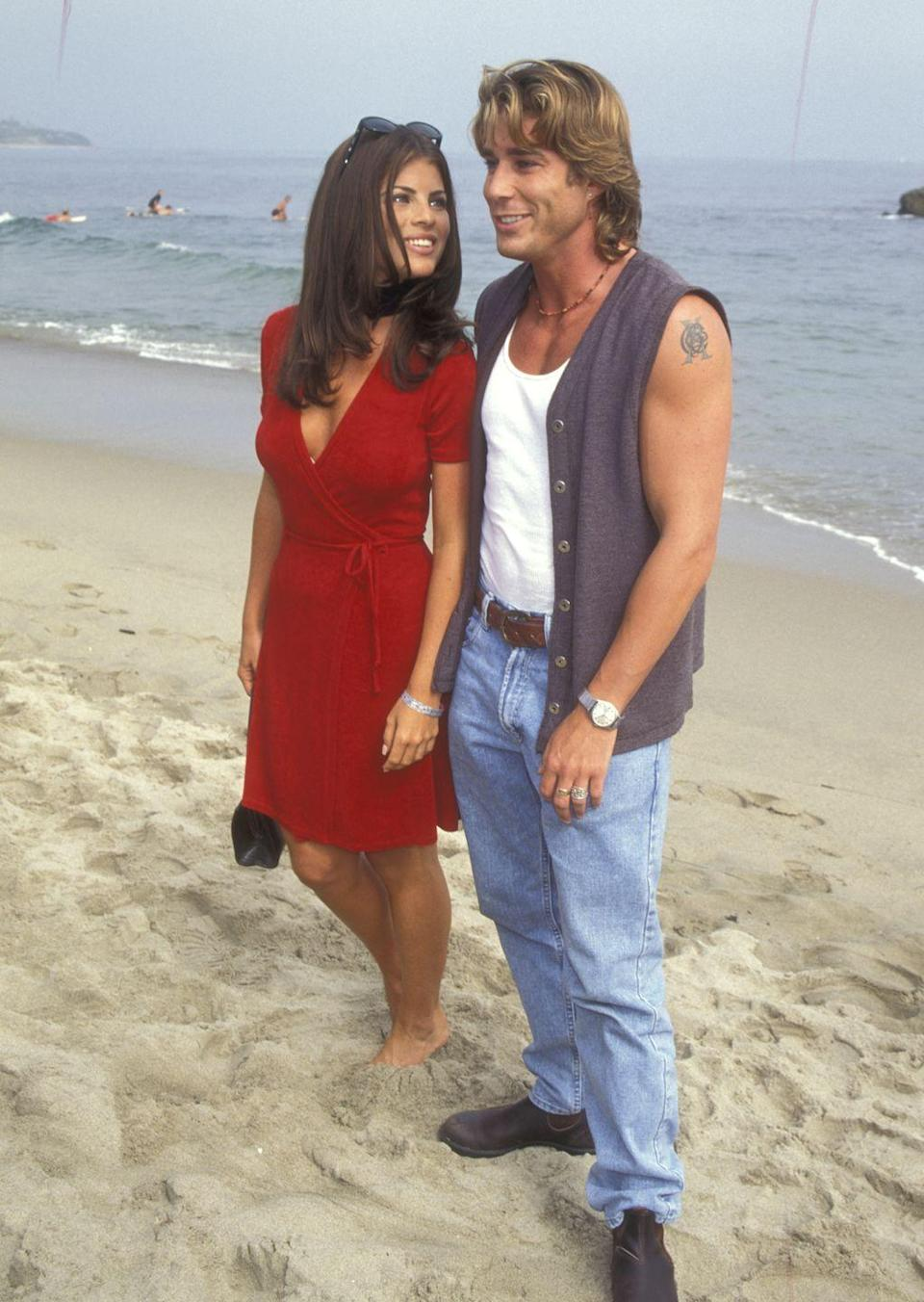<p>A Hollywood party on the beach in the '90s practically requires the cast of <em>Baywatch</em>. Here, Yasmine Bleeth and Jaason Simmons (aka lifeguards Caroline Holden and Logan Fowler) pose for the camera while standing on the shore. </p>