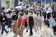People make their way on a street in Tokyo Sunday, Aug. 2, 2020. Confirmed coronavirus cases are hovering at near record levels in Japan, raising worries the pandemic may be growing more difficult to control. The Tokyo government reported more than 290 new cases Sunday, about half in their 20s. (Kyodo News via AP)