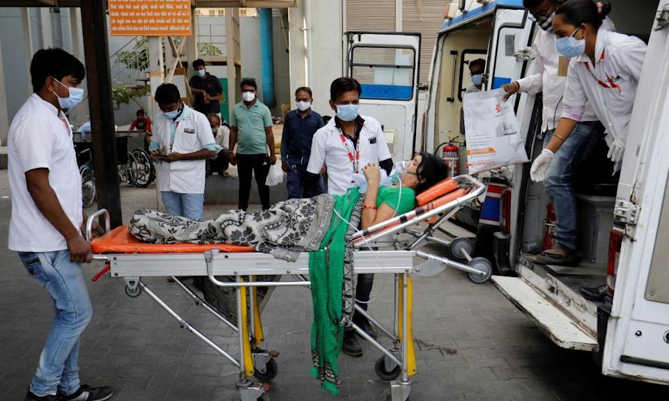 A patient wearing an oxygen mask is wheeled inside a Covid-19 hospital for treatment in Ahmedabad.