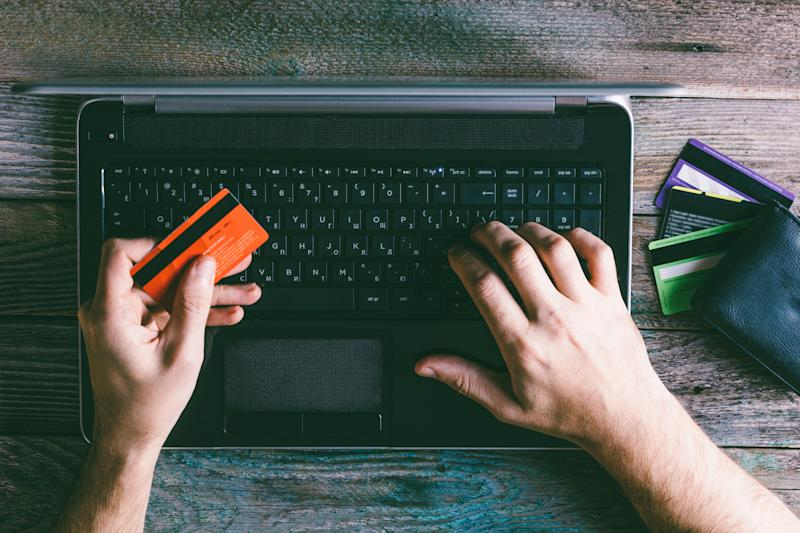 Man holding credit card in left hand while using laptop with his right one.