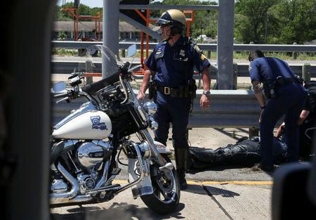 Police officers tend to fallen colleague after police motorcycle accident during Trump motorcade in Louisiana