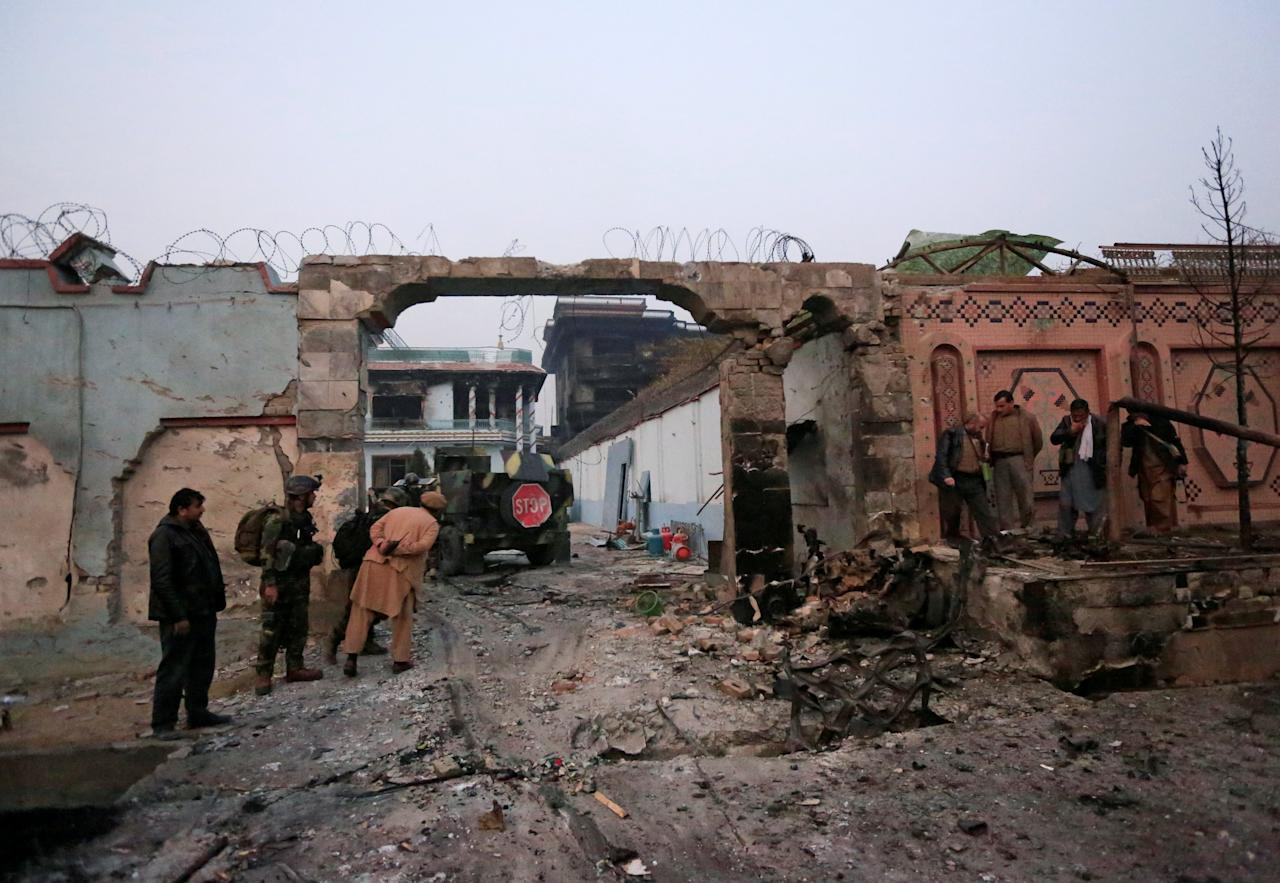 <p>Afghan officials inspect the entrance gate of Save the Children Aid group in Afghanistan, after a blast and gun fire in Jalalabad, Afghanistan, Jan. 24, 2018. (Photo: Parwiz/Reuters) </p>